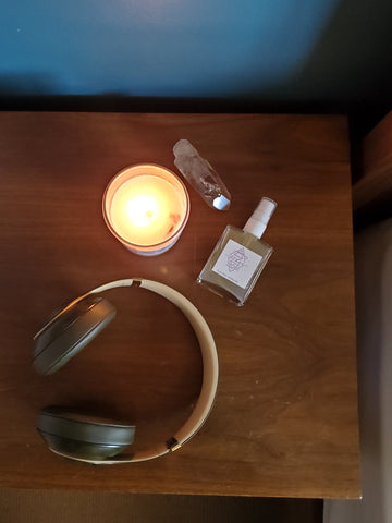 top view of luxury soy crystal candle ritual mist raw gemstone and headphones on wooden nightstand