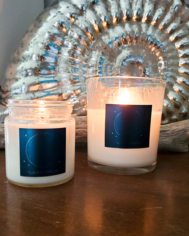 two luxury soy lunar candles on wooden surface with mirrored shell in the background