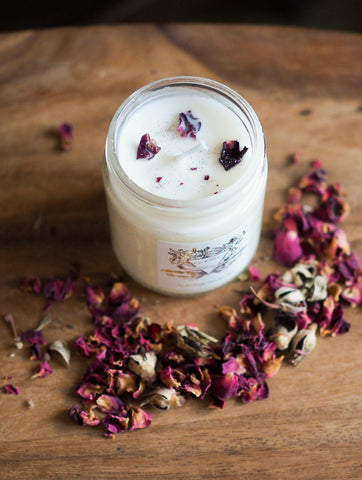 water sign intention candle on wooden tray surrounded with dried rose petals