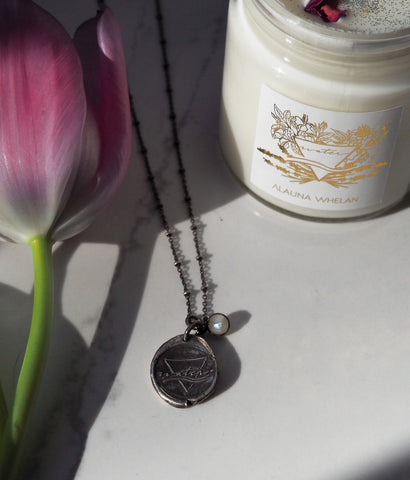 water sign medallion layering necklace with candle and fresh tulips