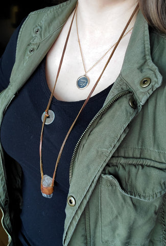 raw crystal and leather necklace layered over silver medallion necklace on woman in black and green top