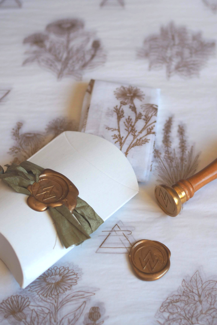 botanical tissue paper with box wrapped in silk ribbon with gold wax seal