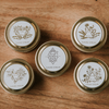2 oz gold travel tin candles with gold foil labels