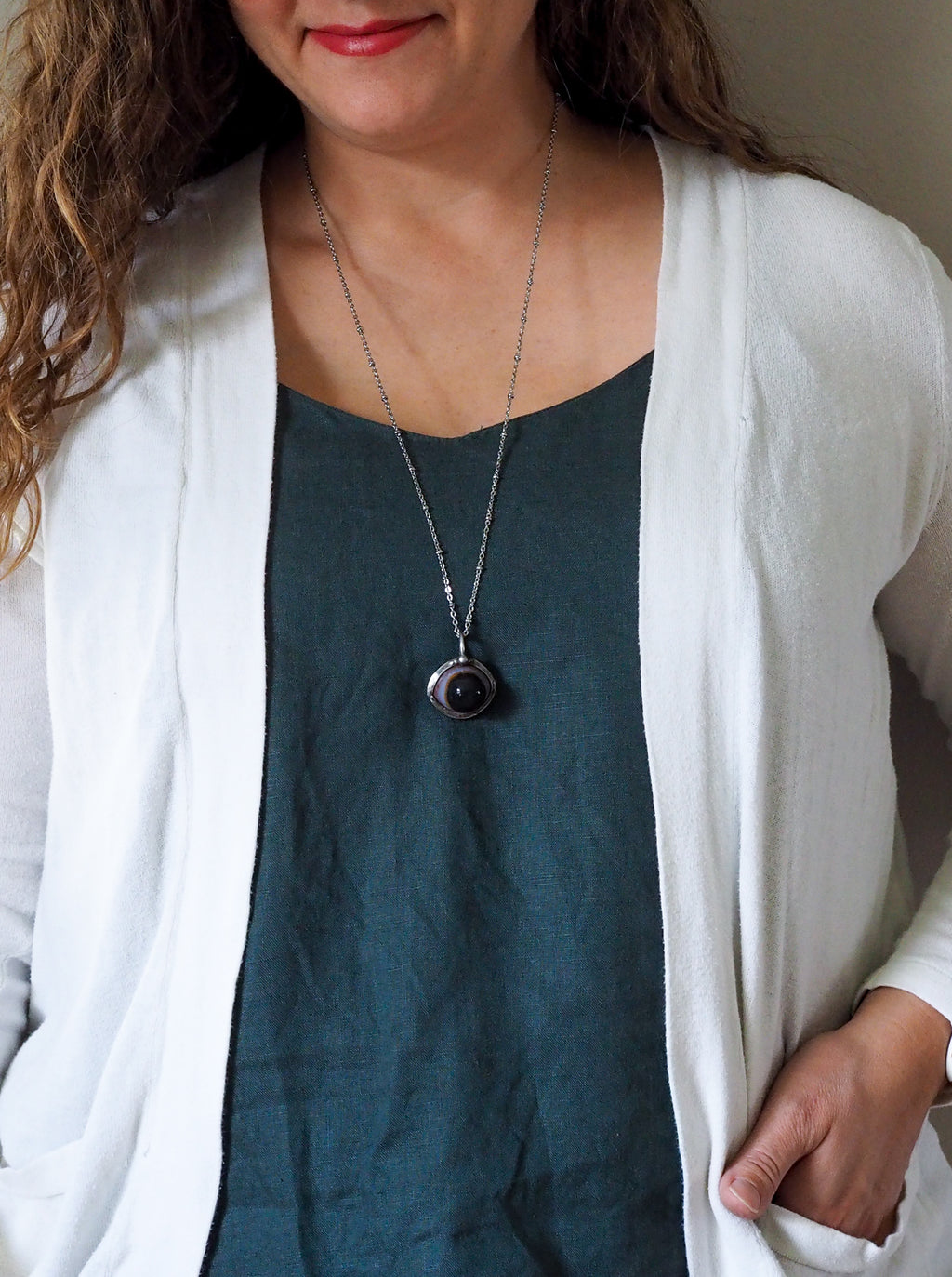 agate eye crystal talisman necklace on woman in blue top