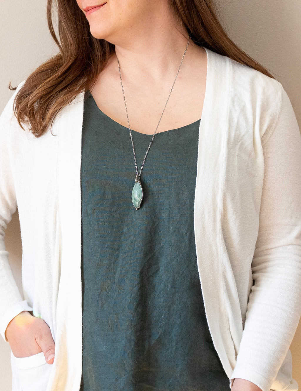 raw aquamarine pastel blue crystal gemstone talisman necklace on woman in blue top with white cardigan