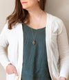 black and red raw crystal talisman necklace on woman in blue top with white cardigan