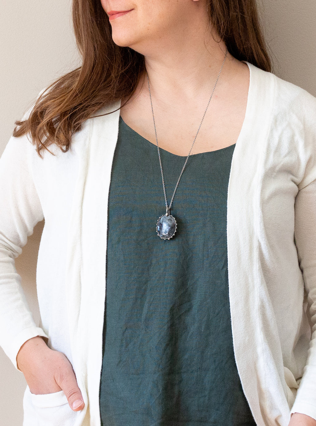 raw black and blue moonstone talisman gemstone necklace on woman in blue top with white cardigan