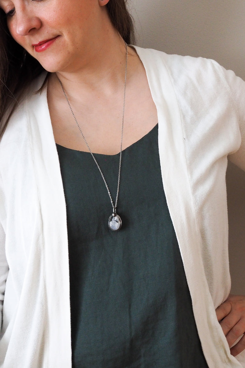 white rainbow moonstone healing crystal talisman necklace on woman in blue top with white cardigan