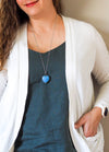 blue gemstone heart crystal necklace talisman on woman in blue top with white cadigan
