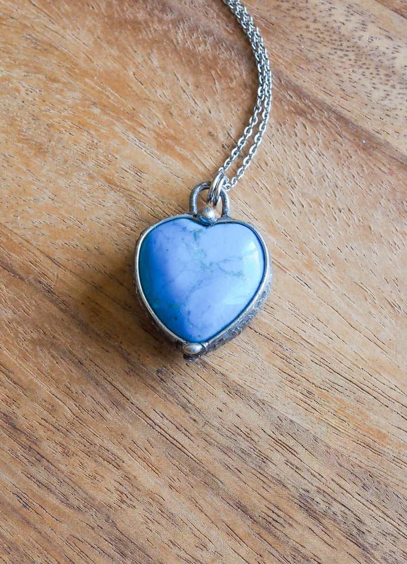 blue gemstone crystal heart necklace talisman on wooden background
