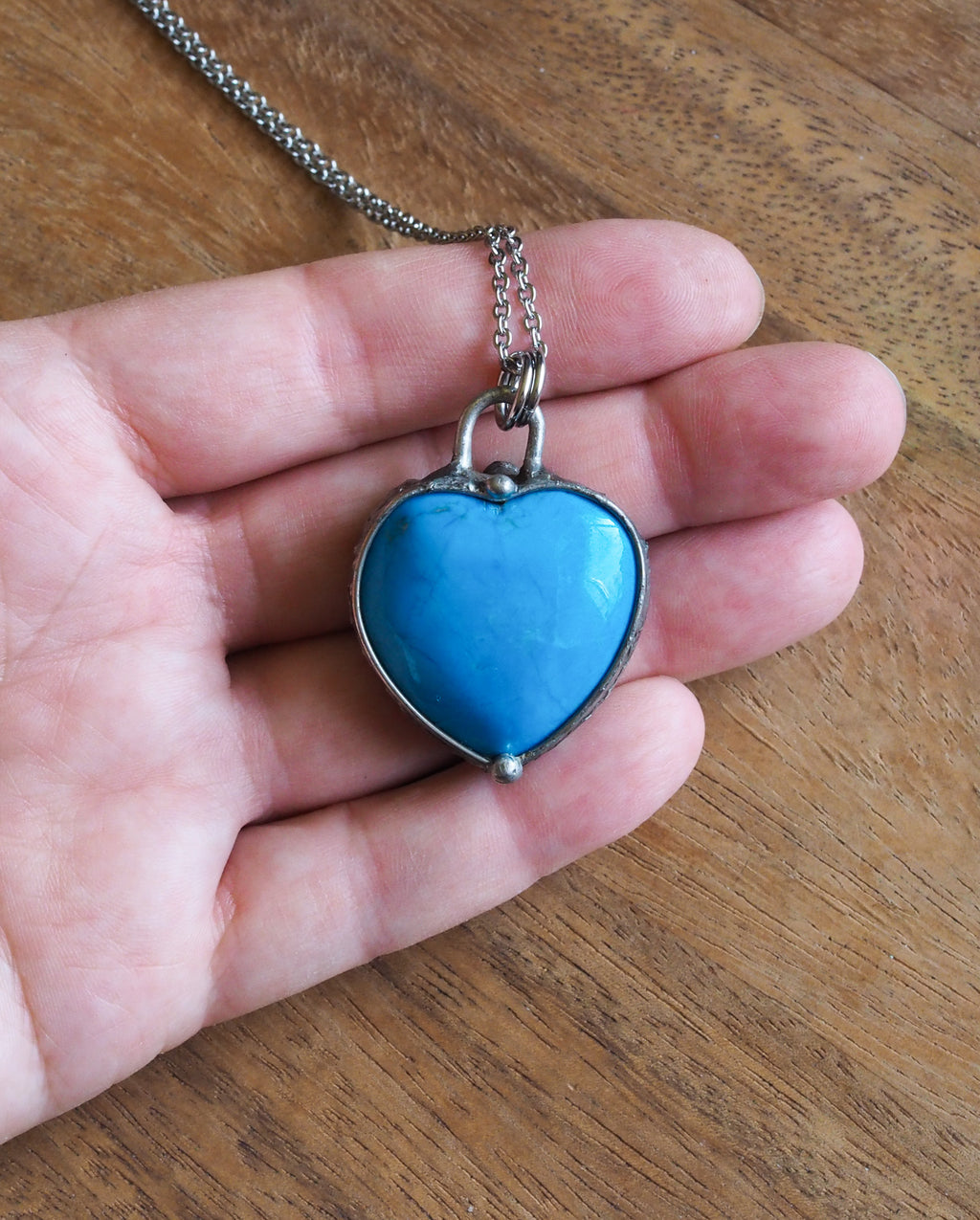 blue gemstone heart crystal necklace talisman in palm of hand