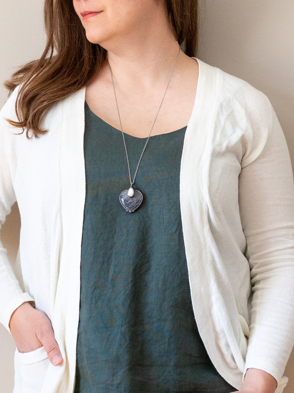 blue and white heart gemstone crystal necklace talisman on woman in blue top with white cadigan