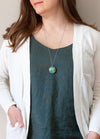 woman in blue top wearing a blue-green turquoise peruvian blue opal talisman crystal necklace