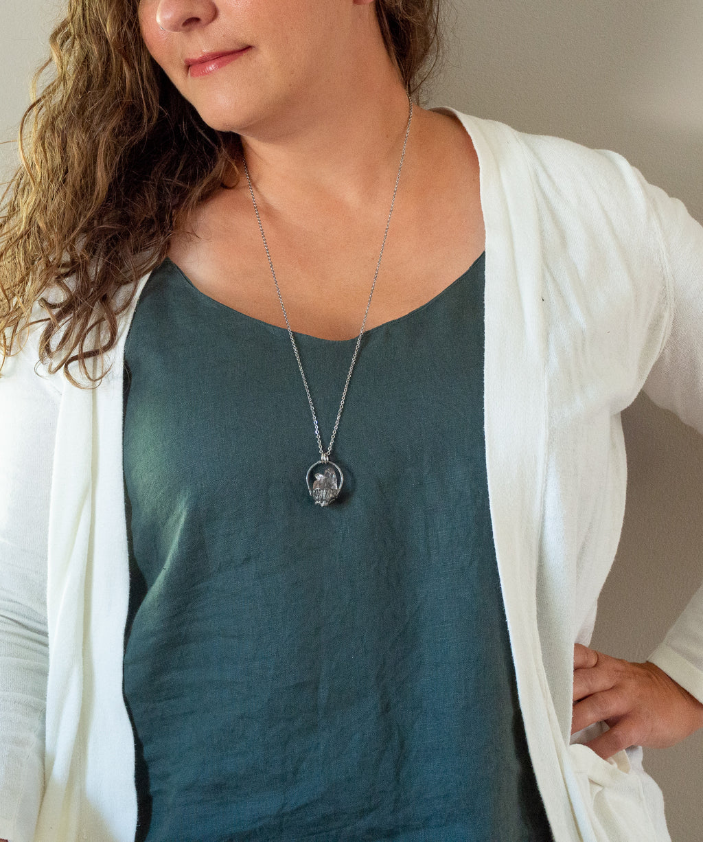 rare light pink brazilian rose quartz gemstone talisman necklace on woman with blue top and white cardigan