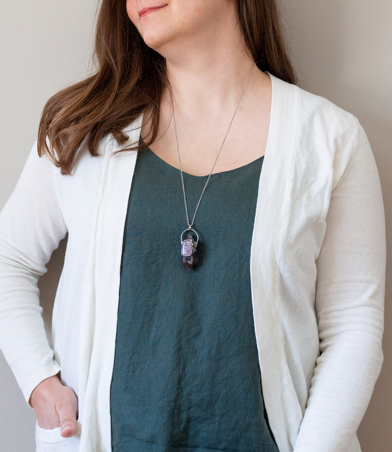 woman in blue top with purple gemstone crystal talisman necklace
