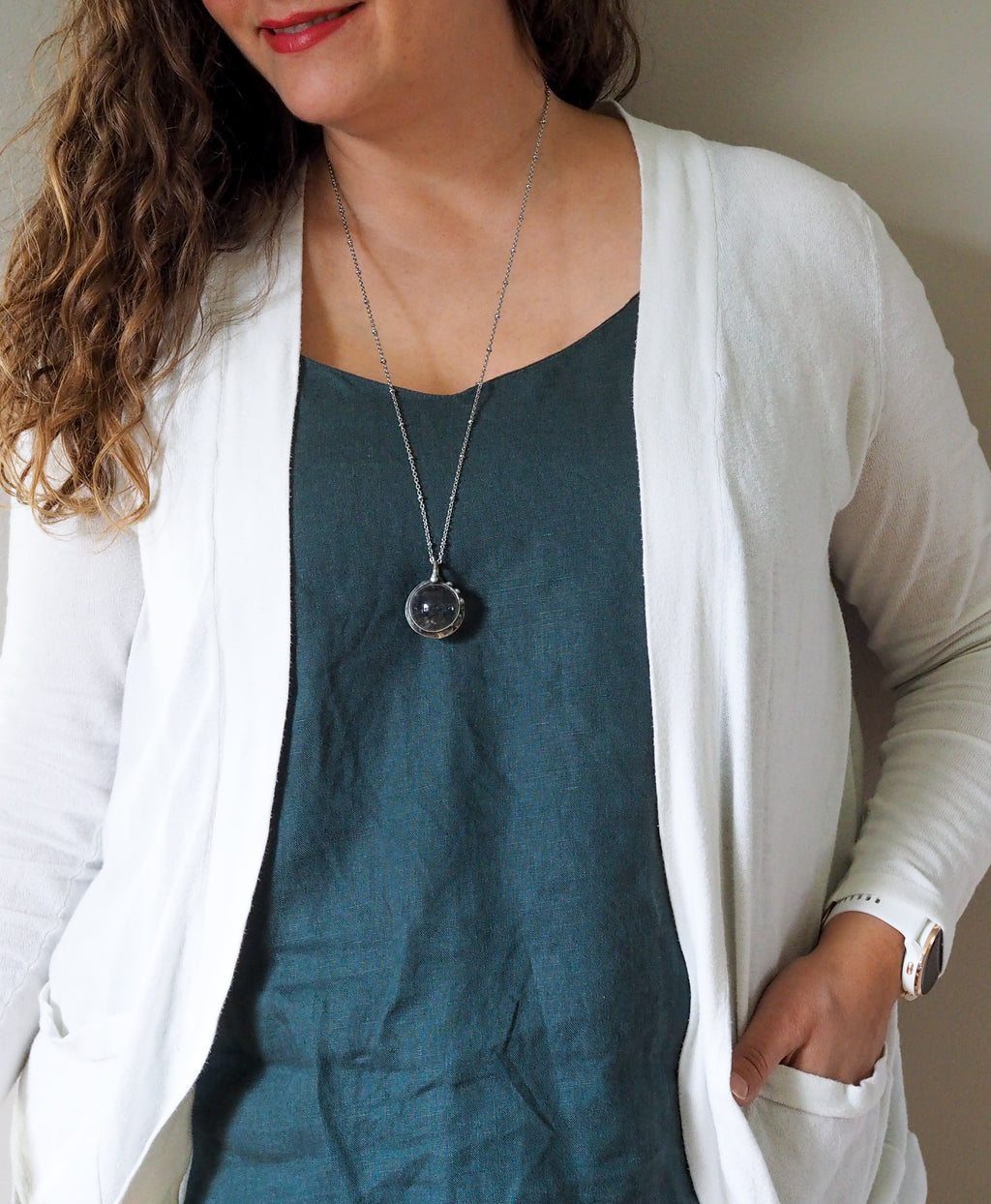 healing crystal orb crystal talisman necklace on woman in blue top