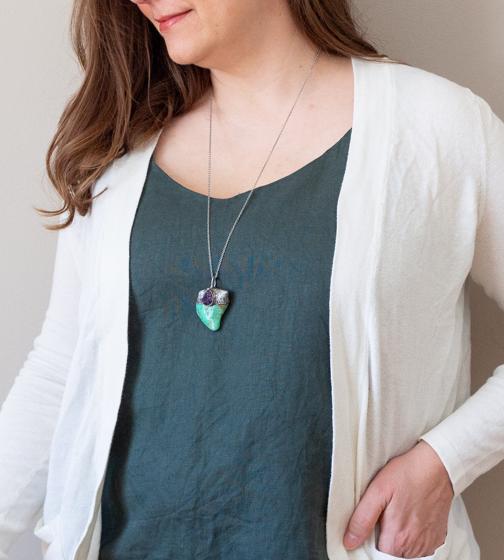 woman in blue top wearing a green chrysoprase and purple amethyst talisman crystal necklace