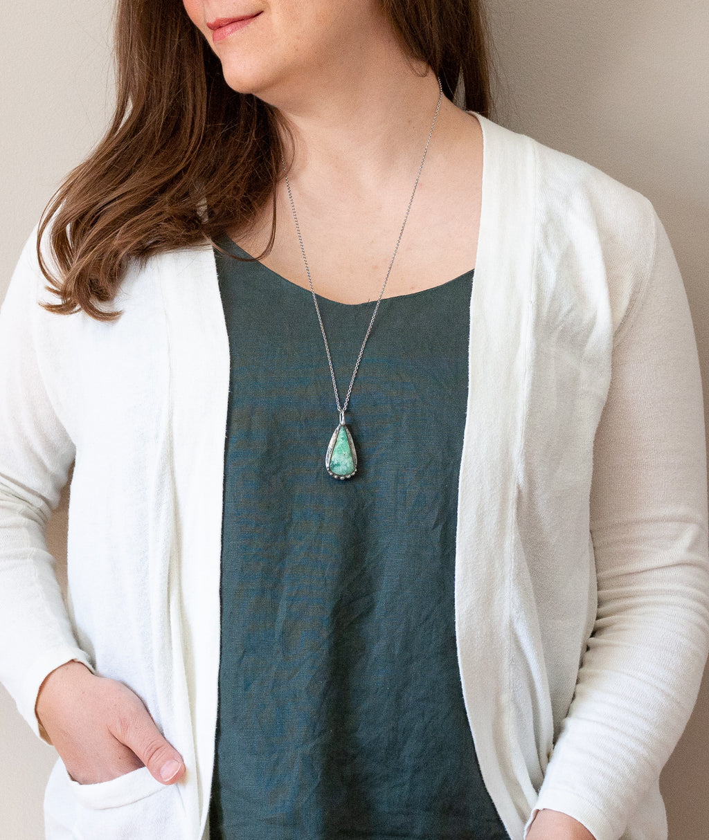 woman in blue top wearing light green turquoise chrysoprase talisman crystal necklace
