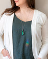 woman in blue top wearing brilliant green malachite talisman crystal necklace
