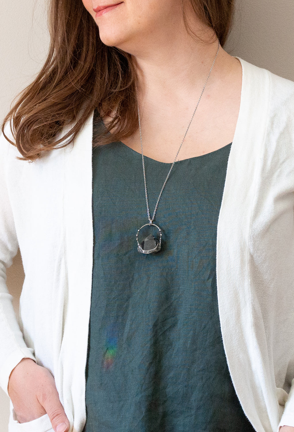woman in blue top with green gemstone chlorite phantom crystal talisman necklace