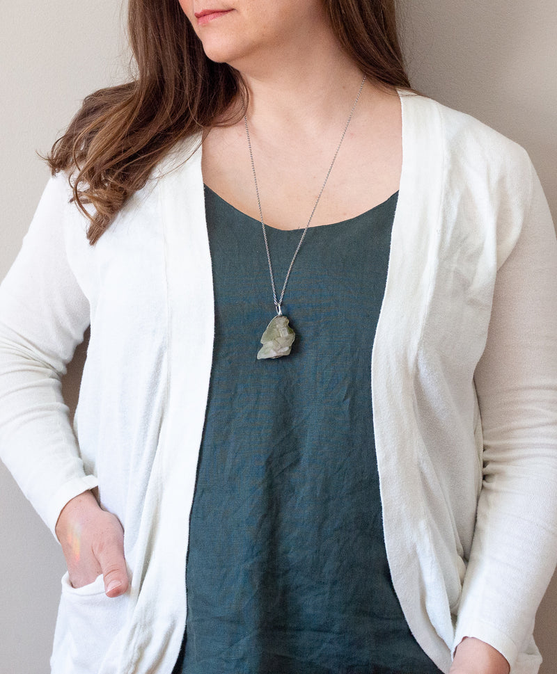 woman in blue top with green gemstone raw chlorite phantom crystal talisman necklace