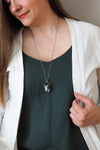 clear quartz and grey moonstone healing crystal talisman necklace on woman in blue top with white cardigan