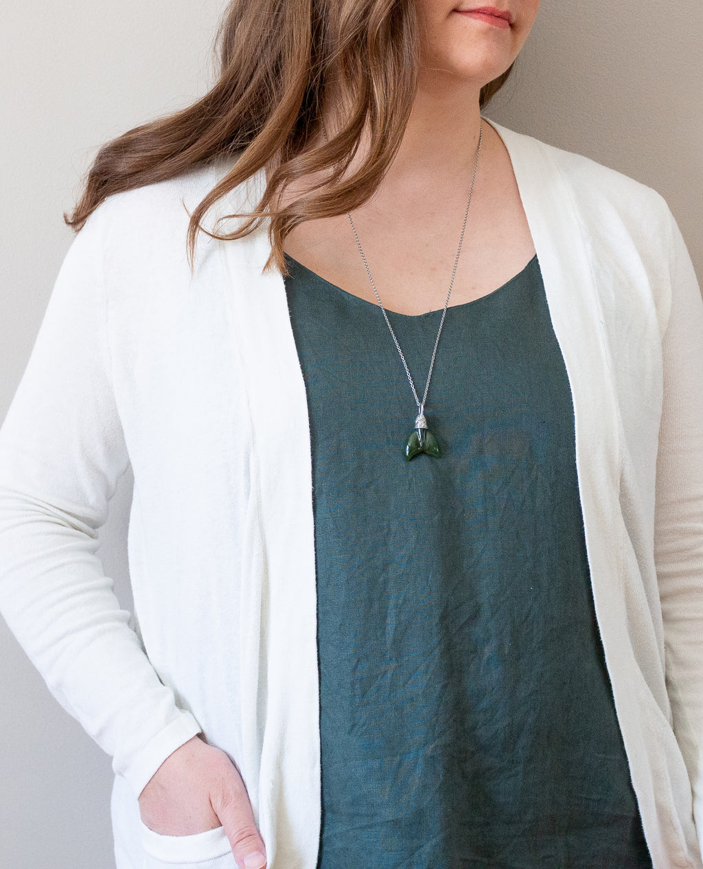 woman in blue top wearing deep green jade talisman crystal necklace