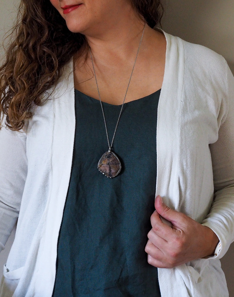 large brown crystal talisman necklace on woman in blue top