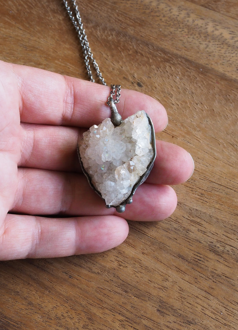 sparkly white healing crystal talisman necklace in palm of hand