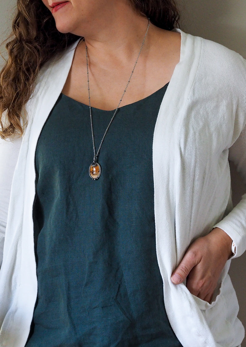 orange crystal talisman necklace on woman in blue top