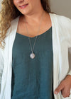 light pink rose quartz gemstone talisman necklace on woman with blue top and white cardigan