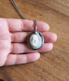 sparkly pale blue healing crystal talisman necklace for peace on palm of hand