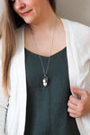clear quartz and peach moonstone healing crystal talisman necklace on woman in blue top with white cardigan