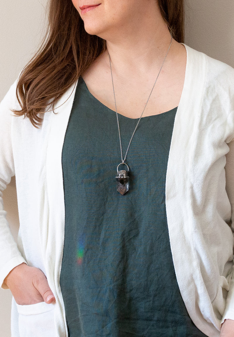 woman in blue top wearing deep green and clear talisman crystal necklace