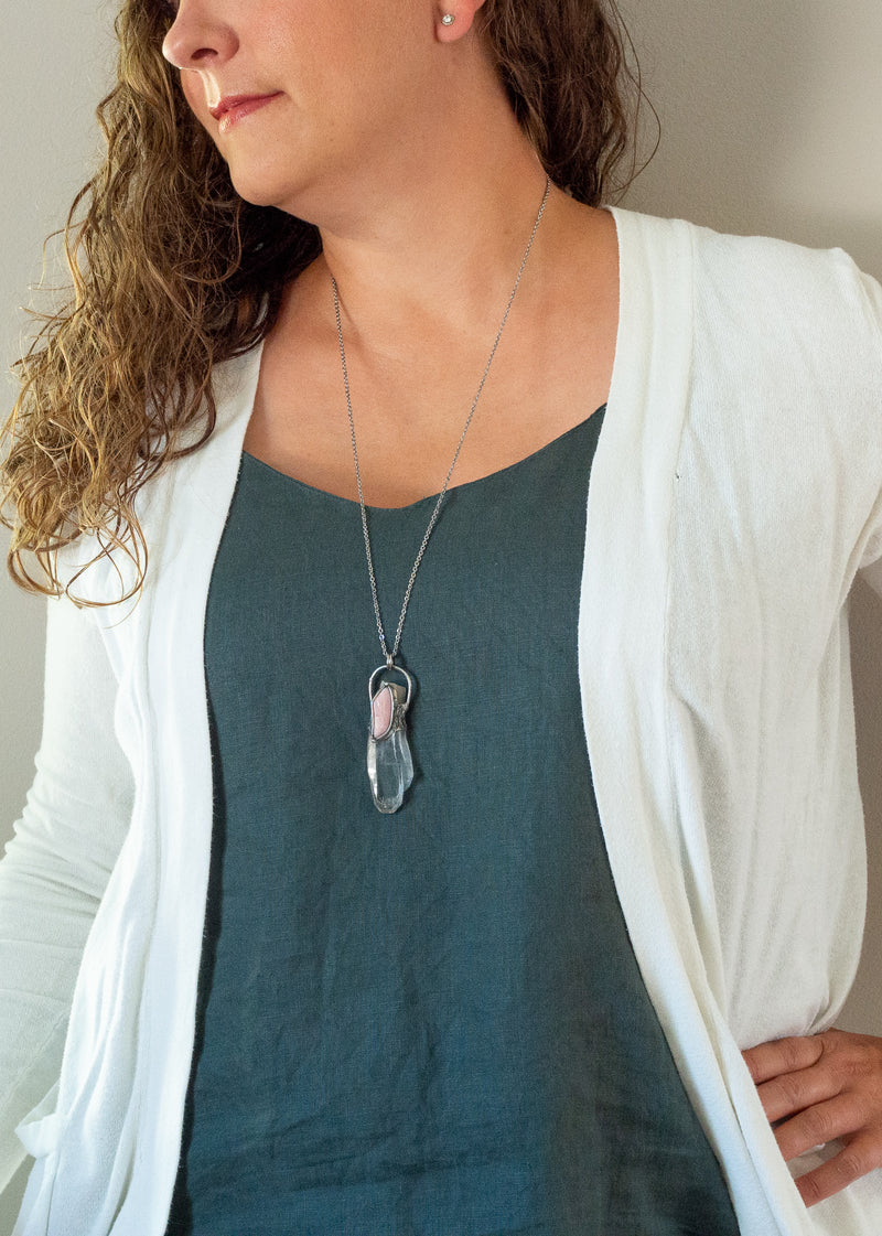 clear and soft pink raw gemstone crystal talisman necklace on woman in blue and white top