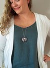 soft pink and blue gemstone talisman necklace on woman with blue top and white cardigan