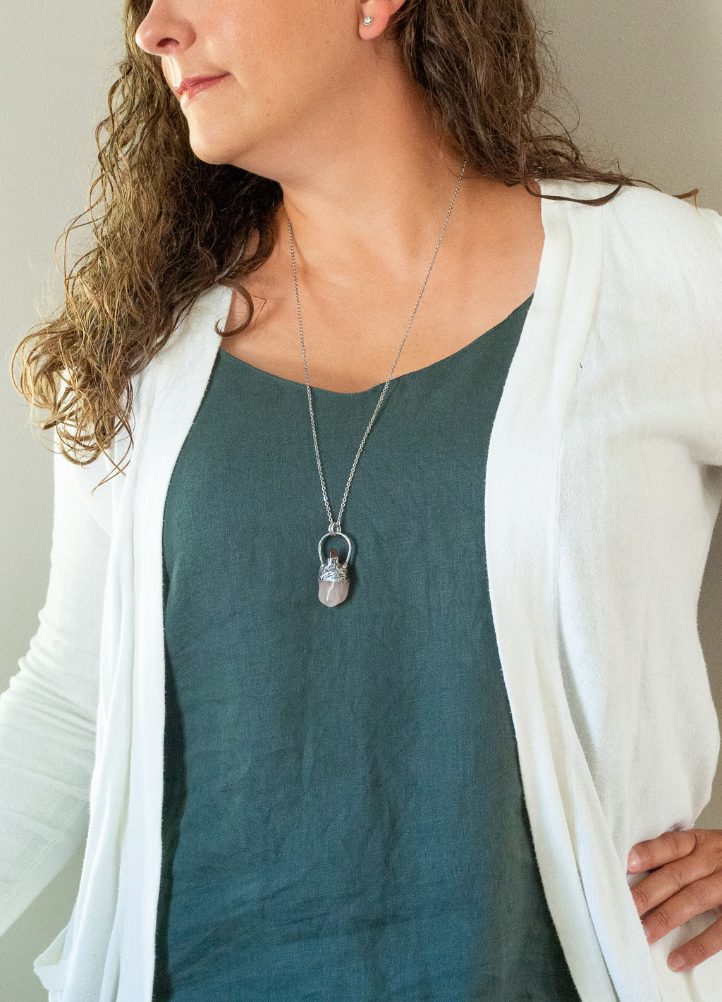 soft pink raw gemstone crystal talisman necklace on woman in blue and white top