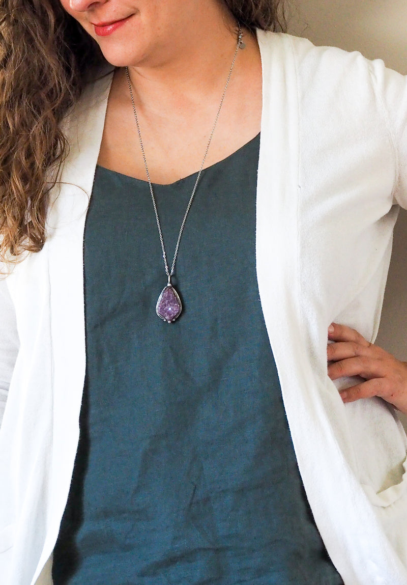 purple crystal talisman necklace on woman in blue top