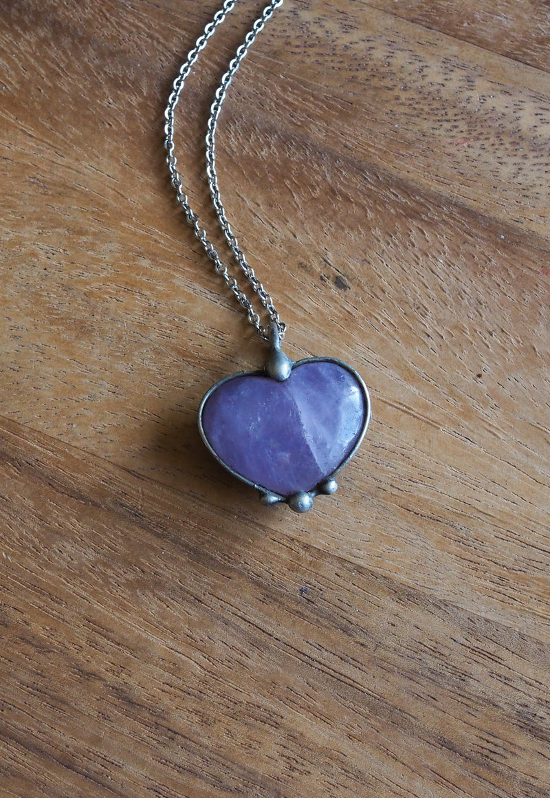 purple amethyst heart crystal talisman necklace on wood background
