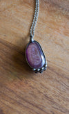 purple gem crystal talisman necklace on wood background