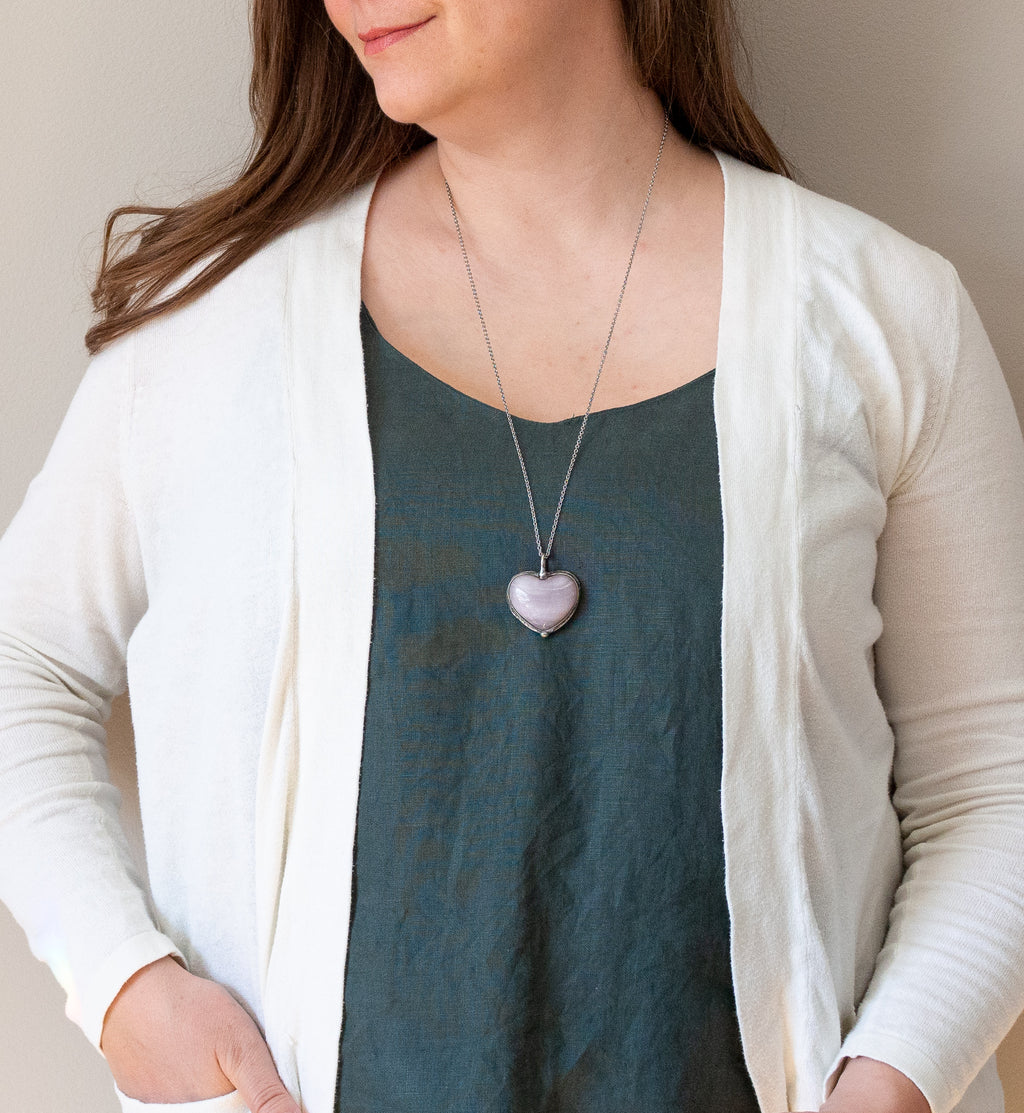 light purple raw crystal heart gemstone talisman necklace on woman in blue top with white cardigan