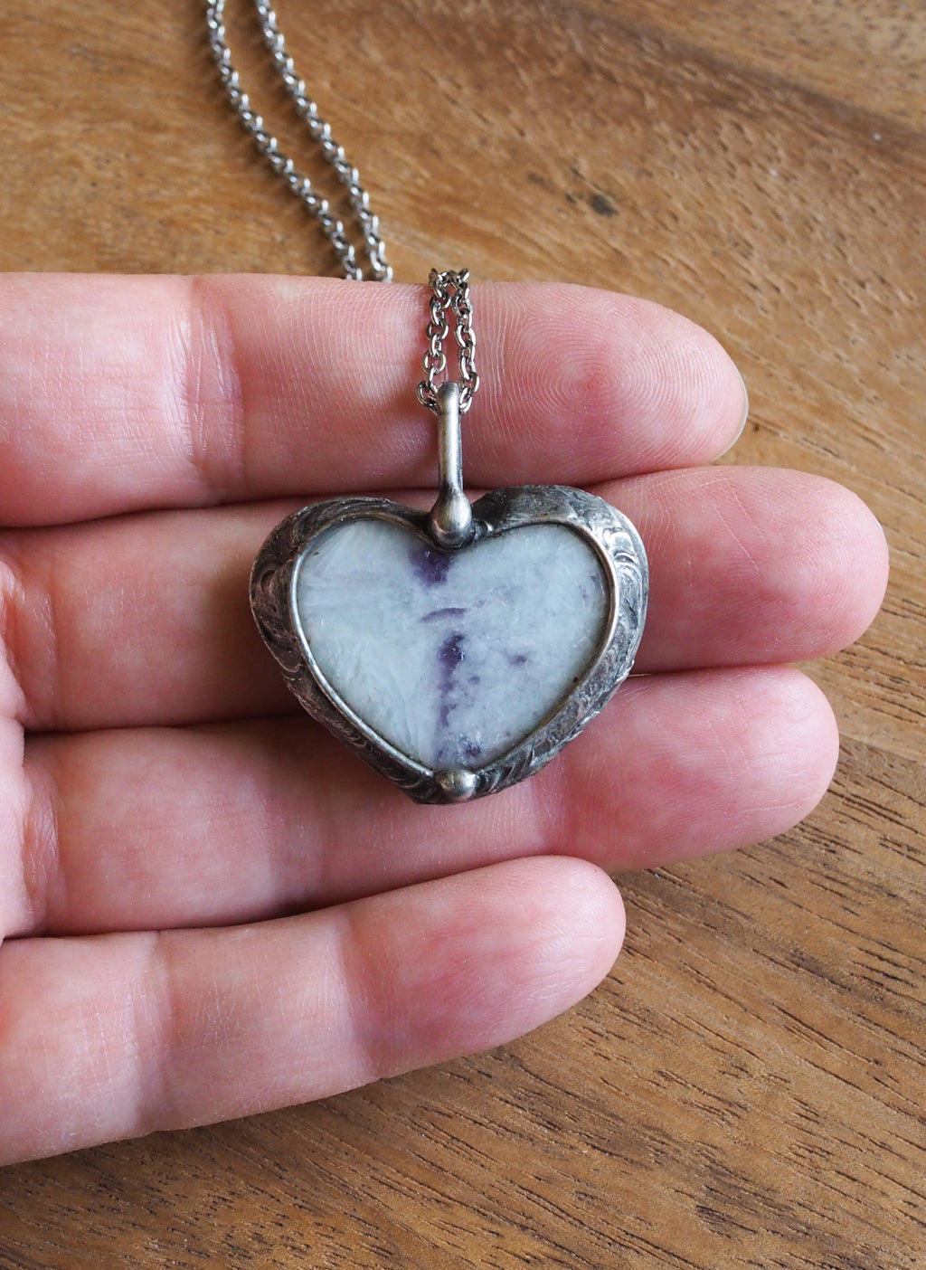 purple and sparkly white heart shaped healing crystal talisman necklace in palm of hand