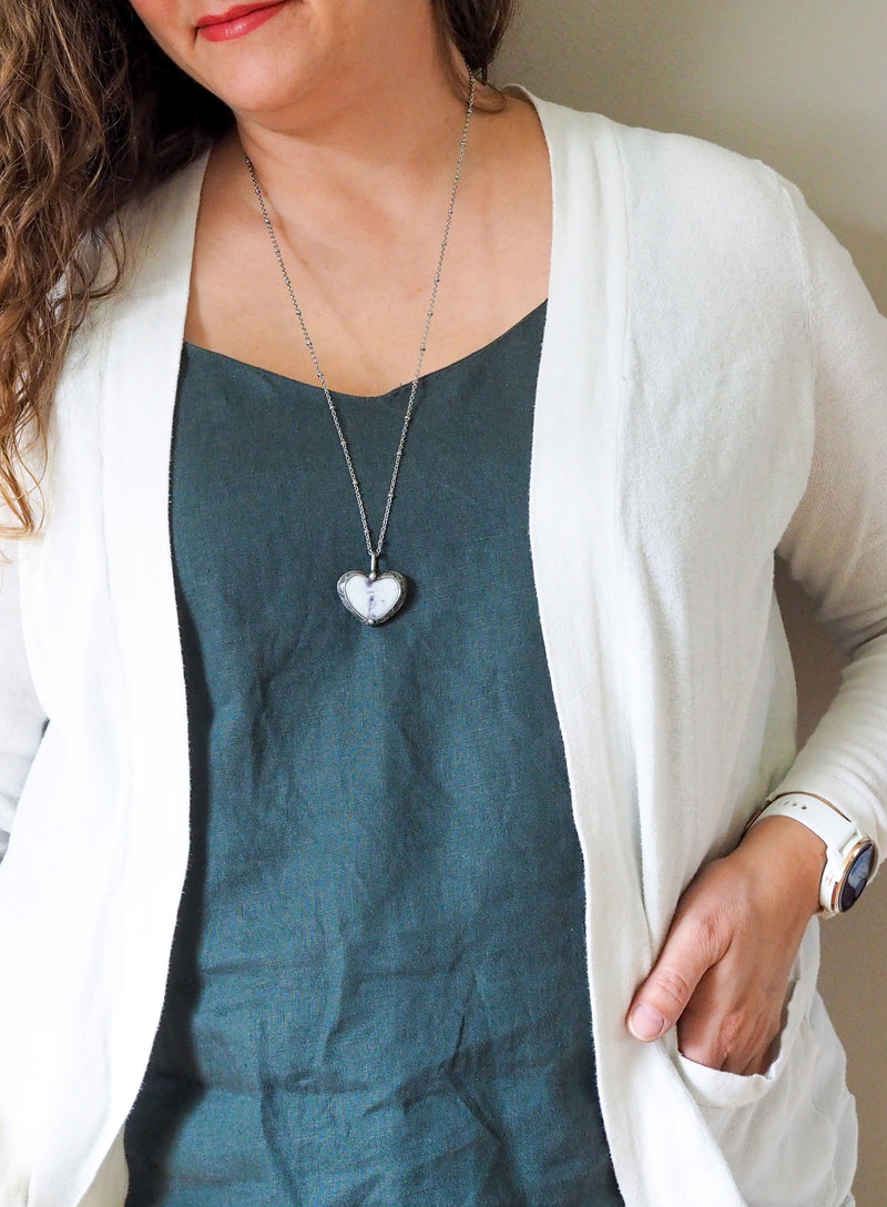 purple and sparkly white heart shaped healing crystal talisman necklace on woman in blue top