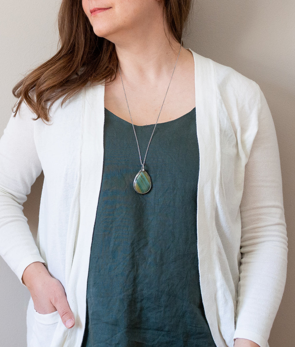 woman in blue top wearing banded gary green jasper talisman crystal necklace