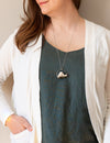 white sparkly spirit quartz raw gemstone crystal talisman necklace on woman in blue top with white cardigan
