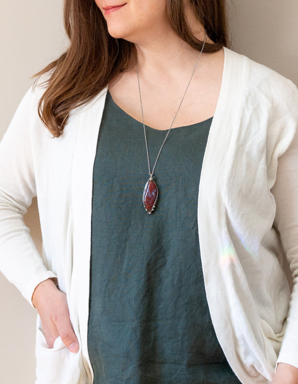 mexican red moss agate gemstone talisman necklace on woman with blue top and white cardigan