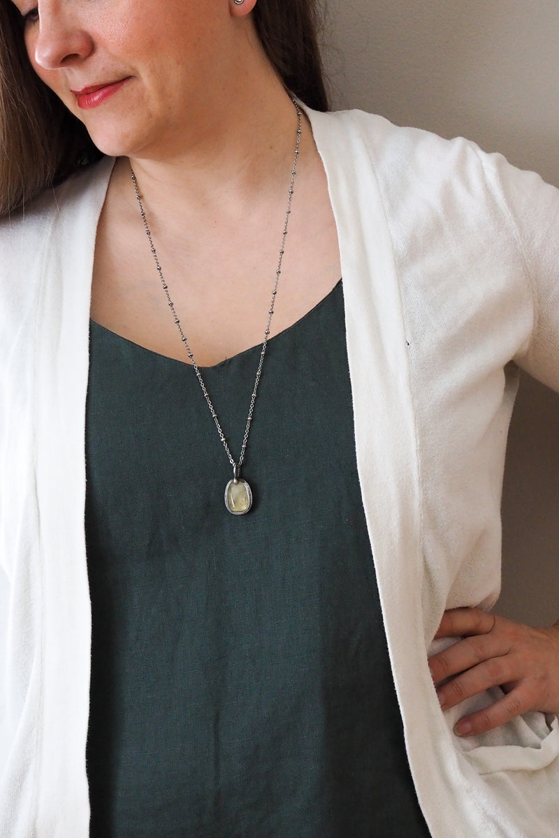 yellow citrine healing crystal talisman necklace on woman in blue top with white cardigan