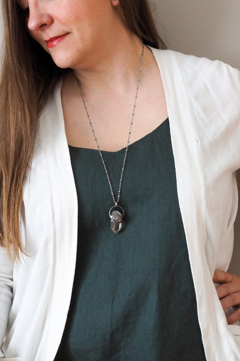 clear quartz and silvery grey moonstone healing crystal talisman necklace on woman in blue top with white cardigan