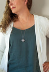 light pink rose quartz heart gemstone talisman necklace on woman with blue top and white cardigan