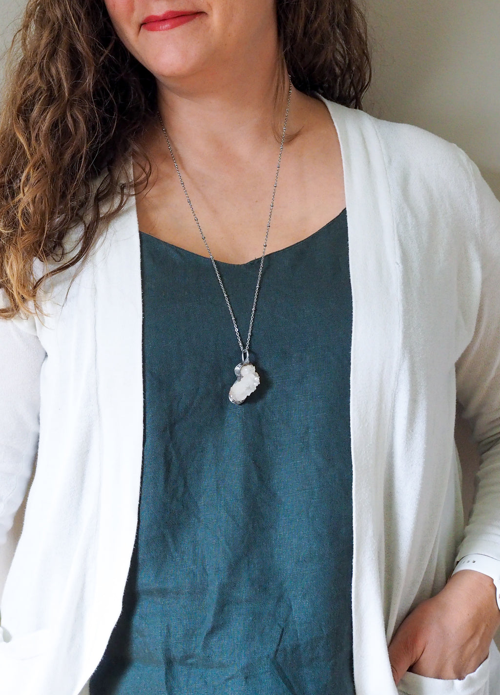 sparkly white healing crystal talisman necklace on woman in blue top